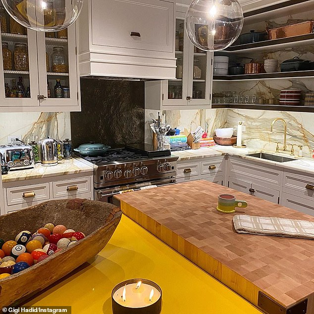 Everything in place: Her inviting kitchen was lit up by large orb light fixtures and had a sizable oven range, plenty of cabinets with chicken wire panels and intriguing uncovered shelves