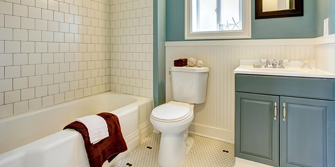 Remodeled Bathroom With Blue Vanity and White Tiles